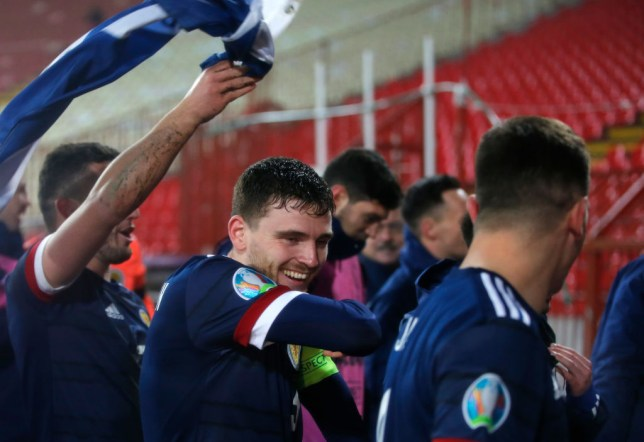 Andy Robertson celebrates with Scotland players after their penalty shootout win over Serbia
