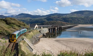 Barmouth, Wales, Bright sunshine, clear skies A train on the Cambrian Coast line crosses the Barmouth Bridge