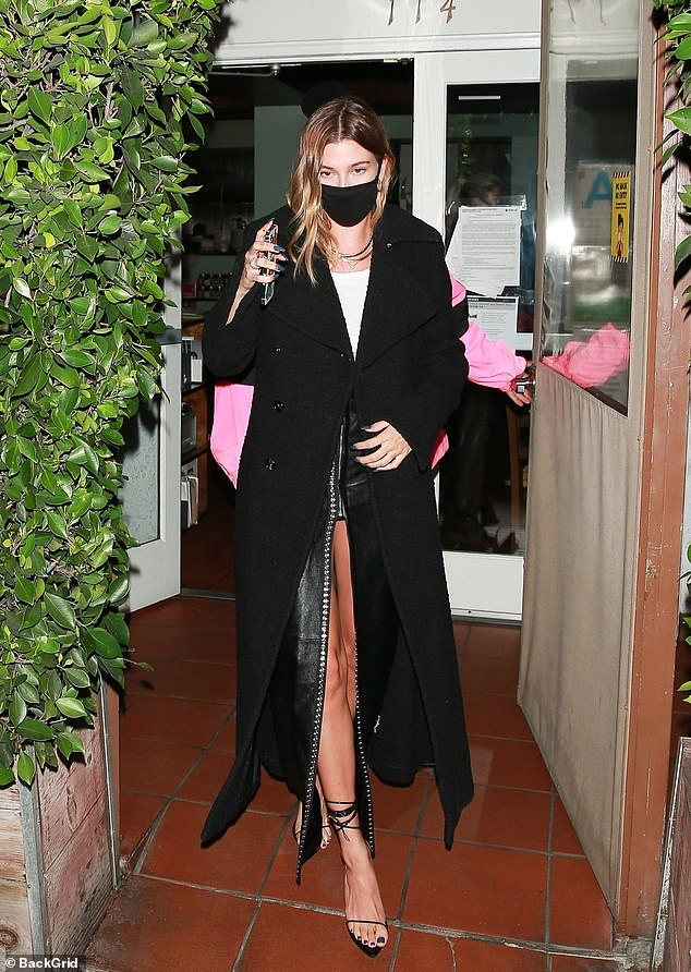 Elegant: Hailey completed her evening look with a long black woolen pea coat, and sexy heeled black sandals that featured a solitary strap over the toes