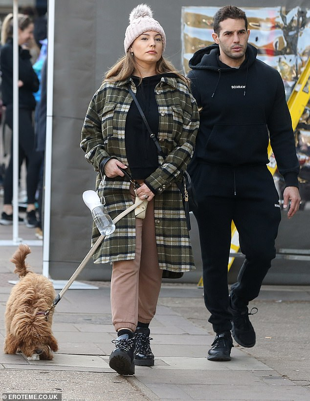 Going for a walk: Kelly wore a cosy black drawstring hoodie and she completed the look with chunky black boots, a shell pink bobble hat, and a leather handbag that draped over her torso