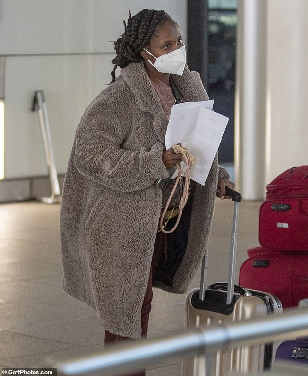 Staying safe:The show judge wore a protective mask as she made her way across a London airport terminal clutching a piece of paper, believed to contain her negative COVID test result