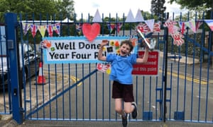 Child jumping with baton in front of school gates decorated with bunting