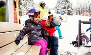 Black father with his multi daughter and son and his caucasian ethnicity wife skiing during an afternoon day