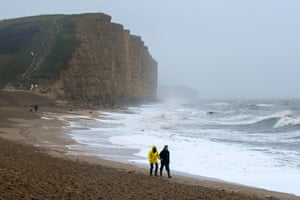 An atmospheric and almost deserted West Bay beach, Dorset, as waves crash ashore.