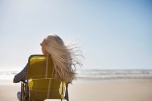 Grey haired women sitting on chair on the beach.