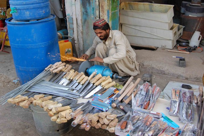 A men busy sharpening knives for customers on the occasion of Eid-ul-Azha. Photo by Matiullah Achakzai/News Lens Pakistan