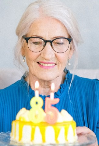 Herbalife Healthy Aging Product Benefits Woman Looking at a Birthday Cake with the Number 85 on it