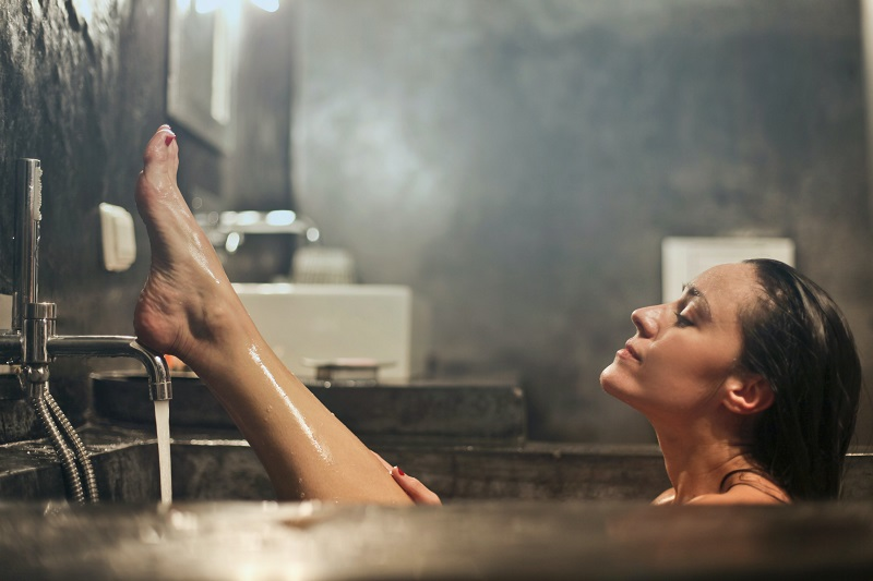 Herbal Aloe Bath & Body Care Products Woman Washing Her Leg in a Bath