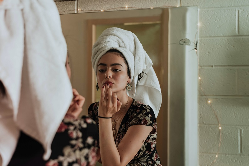 Herbalife Skin Products for Dark Spots Woman Putting Cream on Her Face in a Mirror with a Towel on Her Head