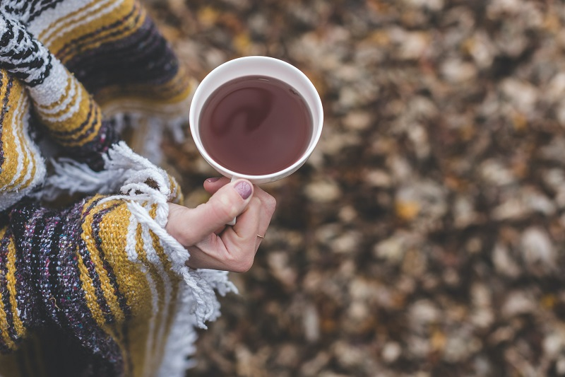 Immune Boosting Tea Recipes Overhead View of a Woman Holding a Cup of Tea Outdoors Wrapped in a Blanket