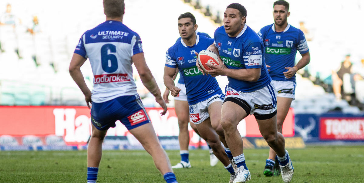 Newtown front-rower Wes Lolo takes the ball forward against Canterbury-Bankstown at ANZ Stadium last Sunday. Jets team-mates supporting Wes are (from left) Tyla Tamou and Will Kennedy. Photo: Mario Facchini, mafphotography