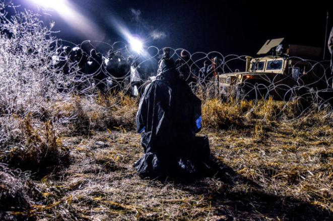 Covered in ice, a water protector kneels in protest at the barrier by the Standing Rock encampment.