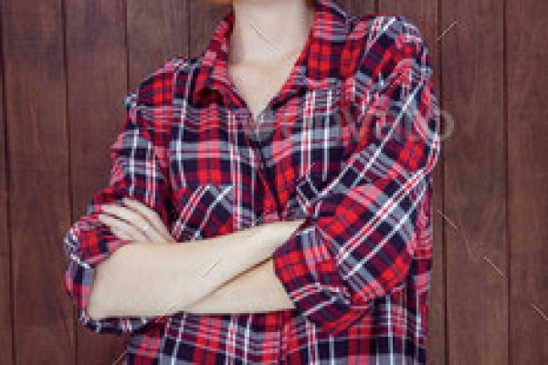 beautiful hipster woman with her arms crossed against a wooden background