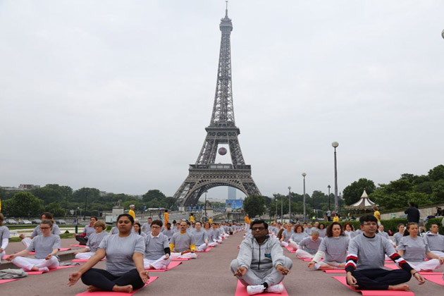 Yoga enthusiasts in Paris with Eiffel Tower in the background