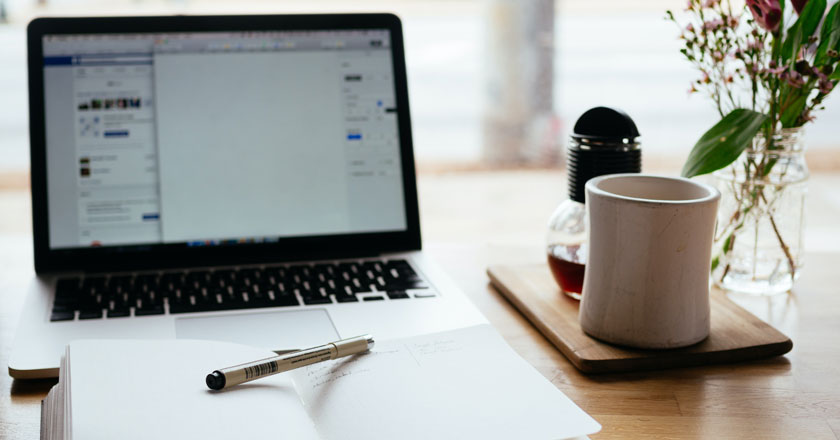 Notizbuch und Teetasse vor aufgeklapptem Laptop - Videokonferenz startet bald