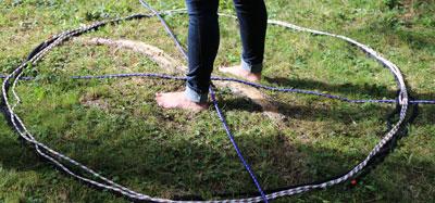 Frau steht barfuß in Piktogramm aus Seilen