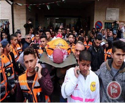 Mizher's body, adorned in PFLP headband and PMRS orange vest, escorted by individuals wearing PMRS uniforms. (Maan News, March 27, 2019)