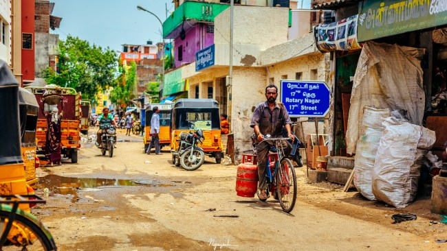 This is a road of a typical neighborhood in Chennai, India. The road can fit two to three auto-ricksaw. On such road, you can find parked vehicles as well as the local traffic.