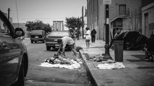 If you think he is rummaging through the trash to find something, you are wrong. He is trying to use magazine book gather the trash and tidy up the trash pile, making conditions more livable.