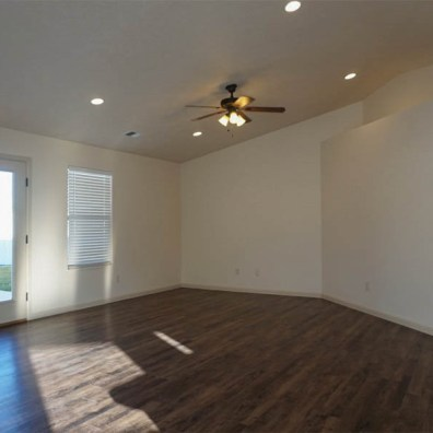 Living room has ceiling fan with light kit & access to back patio