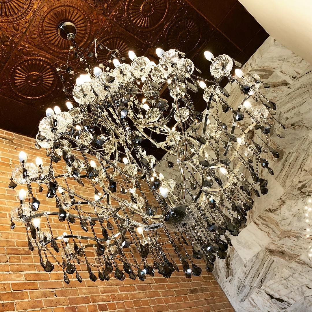 Stairwell Chandelier with old brick, marble tile, & pressed ceiling in a downtown remodel.