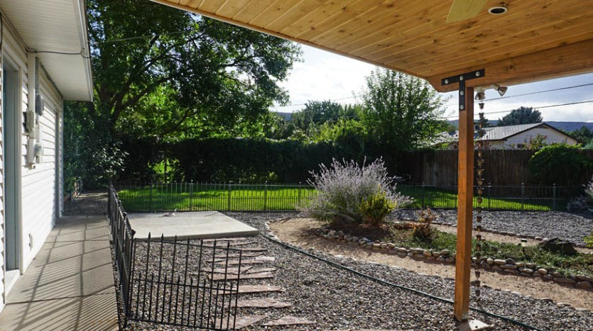 The hot tub pad is accessible via a flagstone path from the covered patio