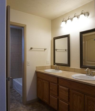 Upstairs hall bath with double sink storage vanity and private toilet/shower room.