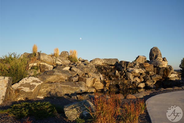 West side of the custom built granite waterfall in the Adobe Falls park at sunset