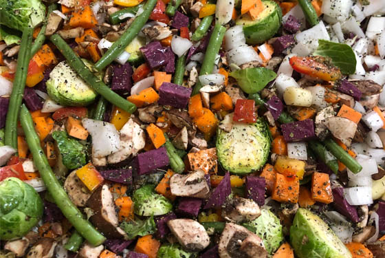 Chopped and seasoned vegetables ready to roast.