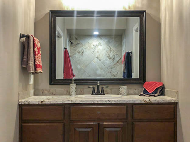 The hall bath is located between the bedrooms, and offers a storage vanity with a single sink, toilet, and in-tub shower with custom tile work.