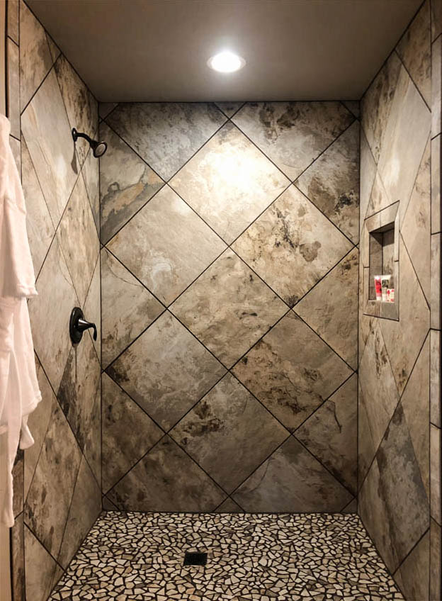 Custom tiled roll-in shower with a built-in shampoo shelf, and sloped tile floorpan.