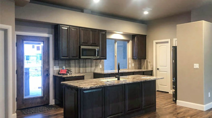 The gorgeous kitchen in 1305 Niblick Way includes GE Slate appliances, a large island, and two pantries!