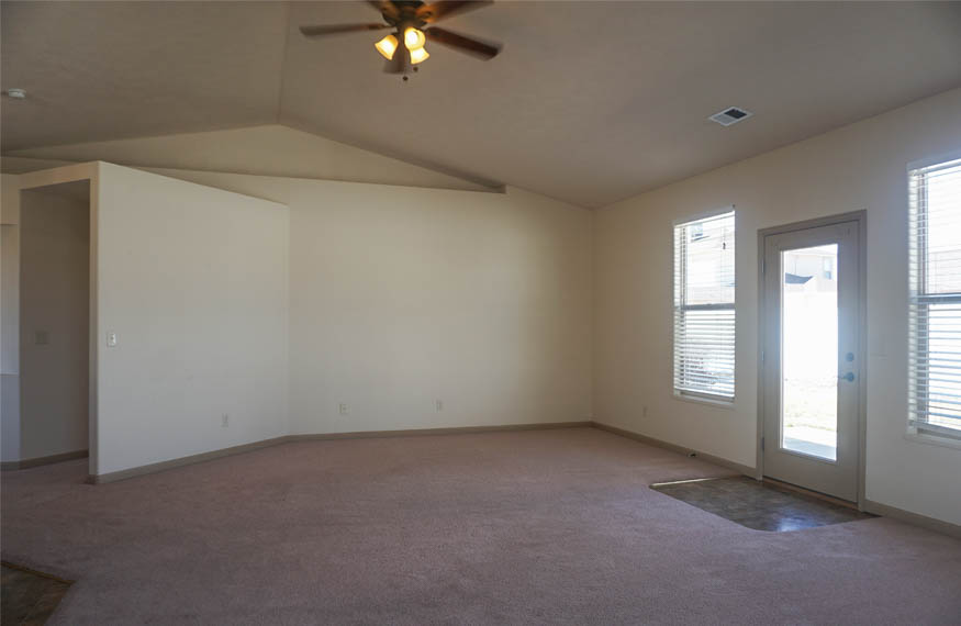The living room of 187 Sun Hawk Drive has a lighted ceiling fan, decorative shelves, and access to the back patio.
