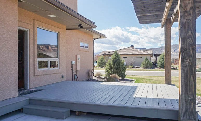 The back patio is built from composite decking, and steps down to the grass and a concrete patio.
