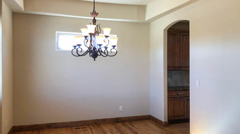 The dining room of 1485 Adobe Falls has a large, tiered chandelier, arhed openings, and large windows to allow in natural light.
