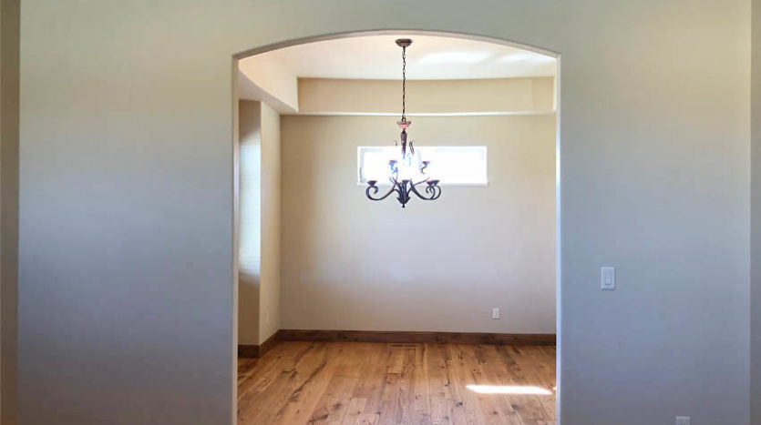 The living room flows into the dining room through an arched opening.