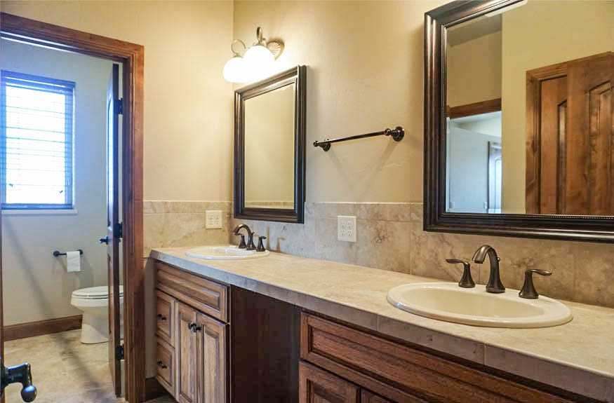 The hall bath in 1485 Adobe Falls Way has a double sink vanity, space for a makeup stool, a linen closet, and private room for the toilet & shower.