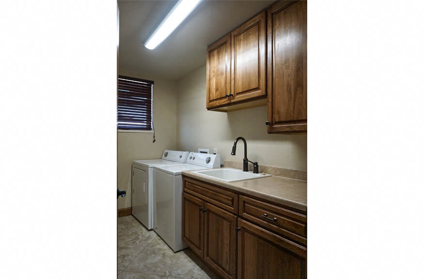 The laundry room in 1485 Adobe Falls Way has built-in cabinetry, a folding area, and space for a full sized washer & dryer. There is an operable window on the north wall for fresh air.