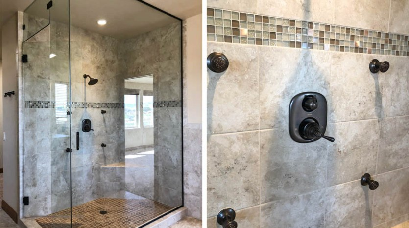 The glass enclosed shower has multiple shower nozzles, a corner seat, and custom tile work.