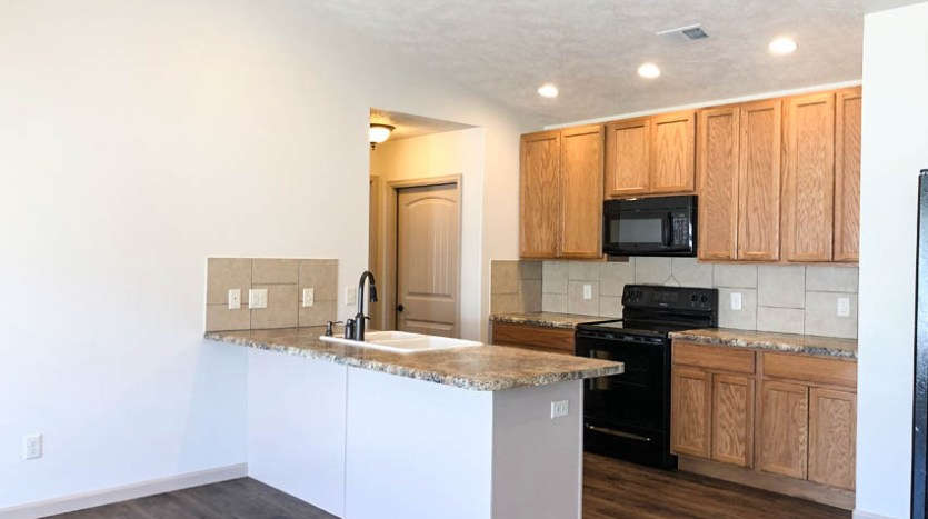 The kitchen includes a breakfast bar and appliances.