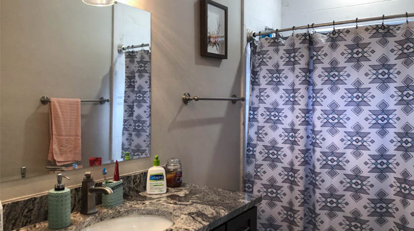 The hall bath has an in-tub shower, granite topped vanity, and linen closet tucked behind the door.