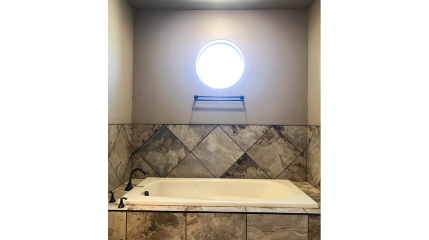 The master tub has a custom tile surround and a round window.