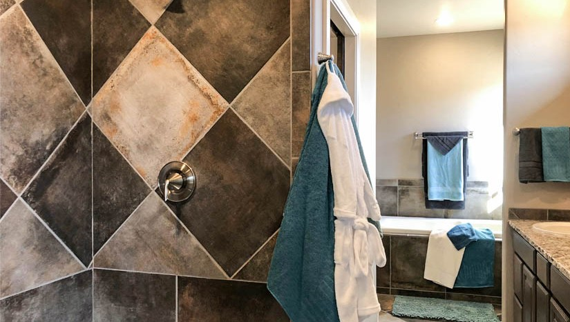 The master bath has custom tile work, a roll-in shower with shampoo cubby, linen closet, double sink storage vanity, private toilet room, and a soaking tub.