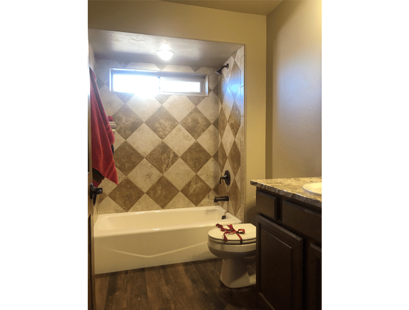 The happ bath of 1404 Shoreline Dr. has a custom tiled in-tub shower, storage vanity, toilet, and linen closet.