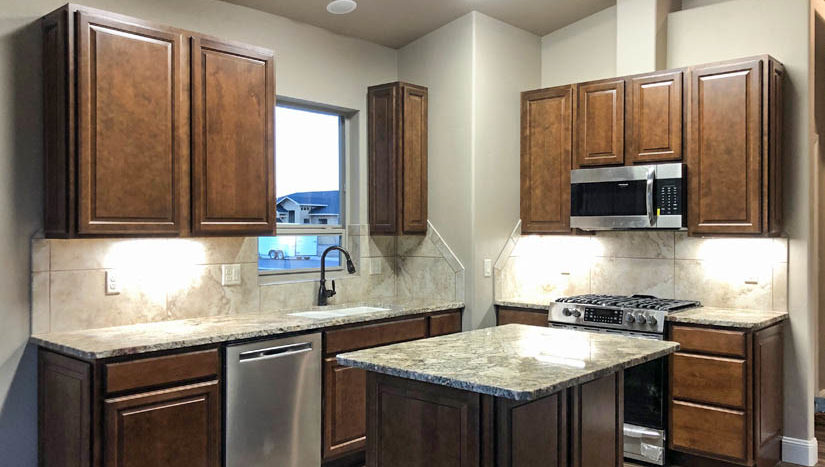 The kitchen in 1404 Shoreline Dr. has stainless steel appliances, a storage island with breakfast bar, and a walk-in pantry.