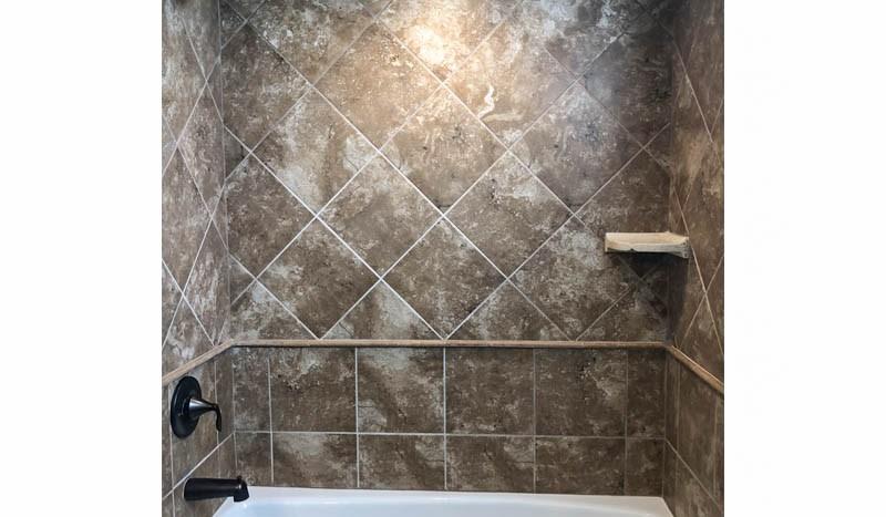The hall bath of 2989 Black Hawk has custom tile work in the in-tub shower.