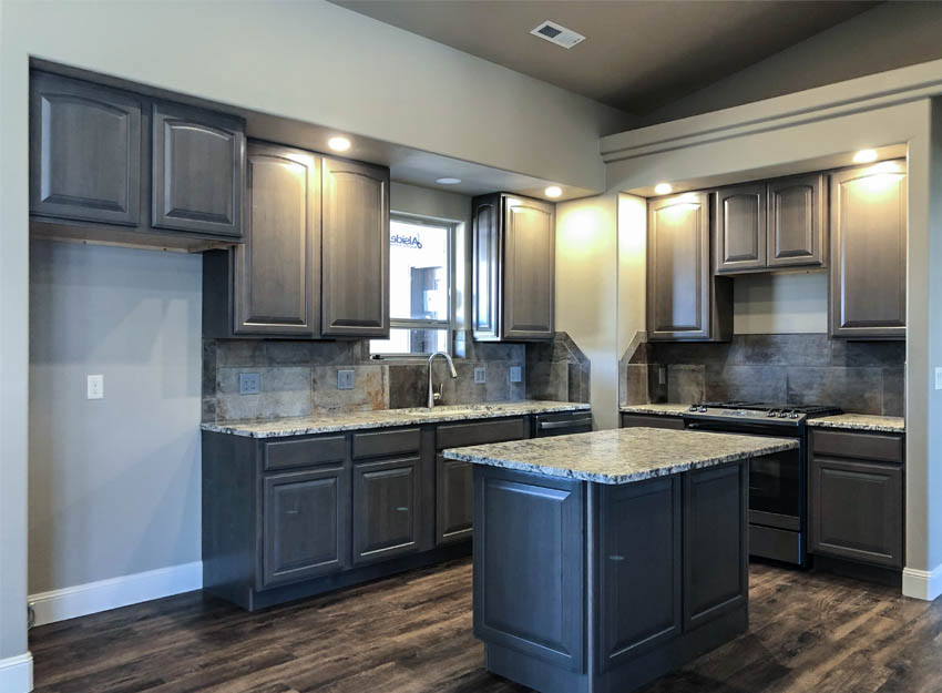 The kithen of 852 Fire Agate features gray stained cabinets, granite countertops, and GE slate appliances.