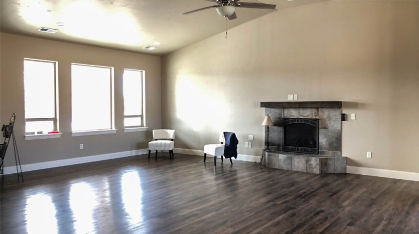 The living room of 852 Fire Agate has vaulted ceilings, a gas fireplace with wood mantle, and large windows looking out onto the front porch.