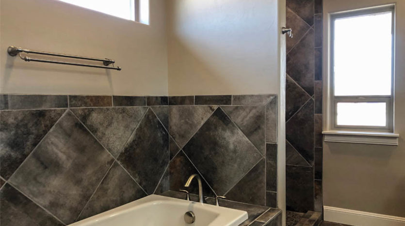 The master bath in 852 Fire Agate has custom tile work around the soaking tub and step-in shower.