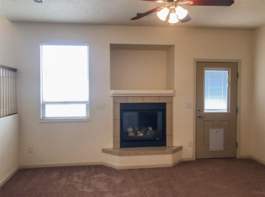 The family room/den of 165 Winter Hawk has a gas fireplace, lighted ceiling fan, and access to the lower patio in the back yard.
